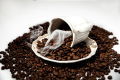 A Cup of coffee beans. Cup of coffee on coffee beans  on white Stock Photography