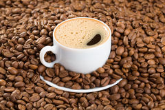 Cup in coffee beans Stock Photography