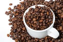 Cup with coffee beans on white background, top view closeup. Cup with coffee beans on white background, closeup Royalty Free Stock Images