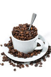 Cup with coffee beans on white background, concept photo. Closeup vertical Stock Photos