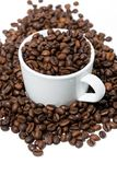 Cup with coffee beans on white background, vertical. Closeup Royalty Free Stock Photos