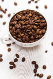 Cup and coffee beans on the white table Royalty Free Stock Photo