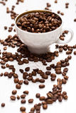 Cup and coffee beans on the white table Royalty Free Stock Photography