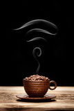Cup of coffee beans with wi-fi icon shaped smoke Stock Image