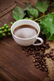 Cup coffee and beans on wood background Royalty Free Stock Images