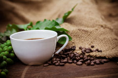 Cup coffee and beans on wood background Stock Photography