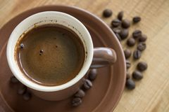 Cup of Coffee with beans on wood background Royalty Free Stock Photography