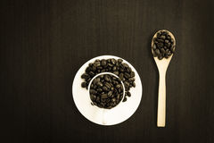 cup of coffee beans with wood spoon on black wooden table. Stock Photo