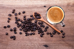 Cup of coffee and beans on wood spoon on wooden background. Stock Photos