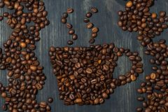 cup of coffee beans on a wooden background, concept photo Stock Images