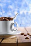 Cup with coffee beans on the wooden table Royalty Free Stock Image