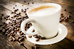 Cup of coffee and beans on wooden table. Stock Photo