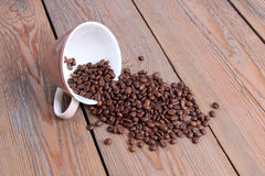 Cup with coffee beans on a wooden table Royalty Free Stock Image