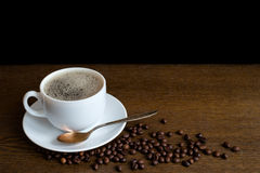 Cup of coffee with beans on a wooden table Stock Photos