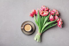 Cup of coffee with beautiful pink flowers for good morning on gray stone table top view in flat lay style. Breakfast on Mother day. Cup of coffee with beautiful Royalty Free Stock Photo