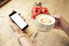 Cup of coffee in beautiful woman hands. Lady using mobile phone internet in cafe. Blank screen for layout. Red roses flowers behin Stock Image
