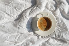 Cup of coffee on the bed with white linen in the room with a lot of natural sunlight, top view. Morning concept royalty free stock image