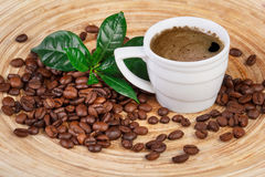 Cup of coffee, beens and leaves Stock Image
