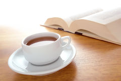 Cup of Coffee and Big Book Leisure on a Wood Table stock images