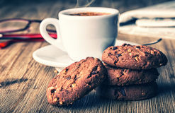 Cup of coffee with biscuit cookies and newspapper. Chocolate biscuit cookies. Chocolate cookies on white linen napkin on wooden ta Stock Images