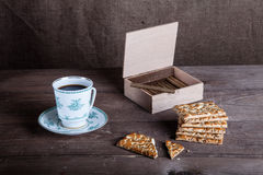 Cup of coffee, biscuits and a box of cigarettes on old wooden ta Stock Images