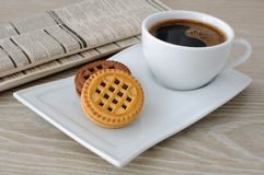 A cup of coffee and biscuits and a newspaper Stock Photos