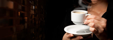 Cup of coffee on black. Background in woman's hands Stock Photography