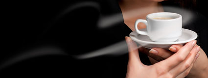 Cup of coffee on black. Background in woman's hands Stock Images