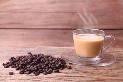 Cup of coffee. Cup of black coffee and coffee beans on wooden background Royalty Free Stock Images