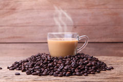 Cup of coffee. Cup of black coffee and coffee beans on wooden background Stock Photos