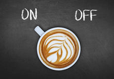 Cup of coffee on black board switching on Royalty Free Stock Image