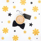 Cup of coffee and black bow tie on white background flat lay. Floral Fathers day still life setup. Happy Father`s Day Background. Cup of coffee and black bow Stock Image