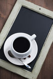 Cup of coffee on black chalkboard, top view Stock Photo
