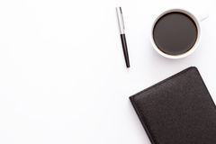 Cup of coffee, black diary and a pen on a white background. Minimal business concept of working place in the office. Royalty Free Stock Photo