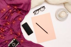 A cup of coffee, black smart, pink paper with new years goals. Scarf and Christmas lights on white background. Stock Photos