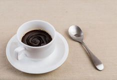 A cup of coffee. A cup of black coffee with spoon on a tablecloth Stock Photography