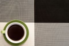 Cup of coffee on the black and white clothtable. Green cup of coffee on black and white tablecloth background. Office Royalty Free Stock Images