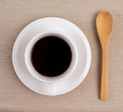 A cup of coffee. A cup of black coffee and wooden spoon on a tablecloth Royalty Free Stock Photo