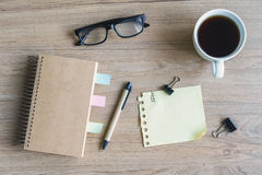 Cup of coffee with blank notebook and notepaper on wooden desk Royalty Free Stock Images