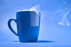 Cup of coffee on a blue background.  Stock Image