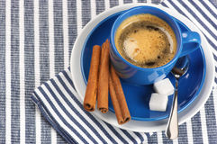Cup of coffee. Blue cup of coffee on blue striped tablecloth Royalty Free Stock Images