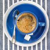 Cup of coffee. Blue cup of coffee on blue striped tablecloth Stock Images