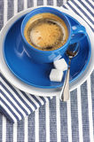 Cup of coffee. Blue cup of coffee on blue striped tablecloth Royalty Free Stock Photography