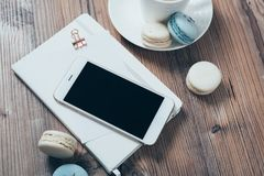 Cup of coffee, blue macaroons and smartphone on wooden table bac Royalty Free Stock Photos