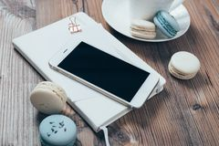 Cup of coffee, blue macaroons and smartphone on wooden table bac Stock Images