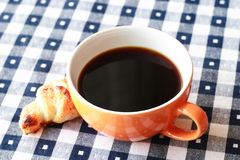 Cup of coffee on blue and white gingham tablecloth Royalty Free Stock Images