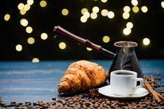 Cup of coffee on a blue wooden table with coffee beans and a croissant and Christmas lights royalty free stock photo