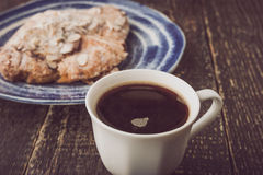 Cup of coffee with blurred croissant  with almond on the blue ceramic plate Stock Images