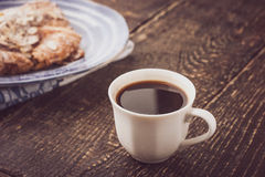 Cup of coffee with blurred croissant   on the blue ceramic plate horizontal Royalty Free Stock Images