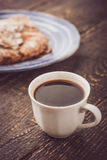 Cup of coffee with blurred croissant   on the blue ceramic plate vertical Stock Photos